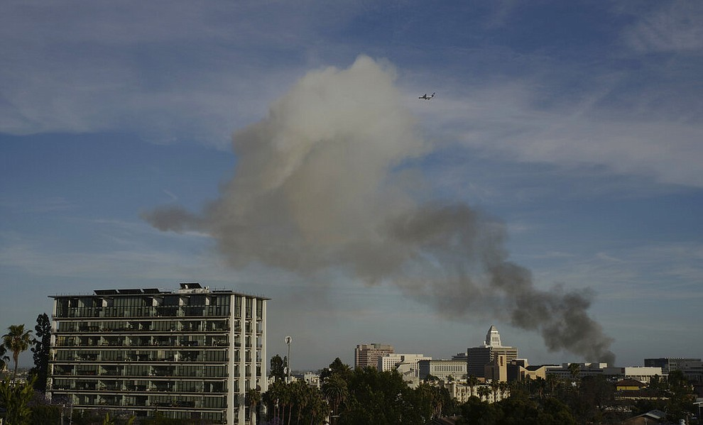 Smoke rises from an explosion at a structure fire Saturday, May 16, 2020, in Los Angeles. (AP Photo/Damian Dovarganes)