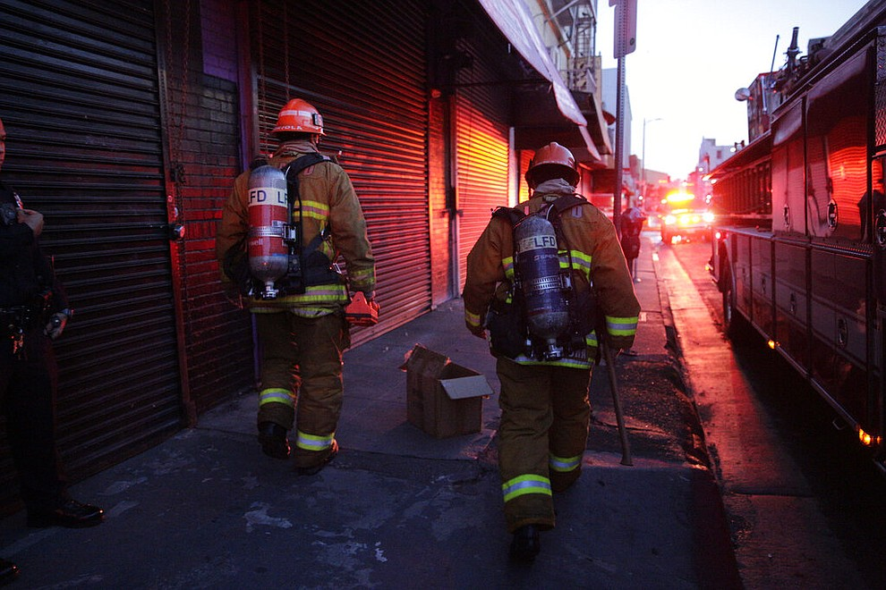 Los Angeles Fire Department firefighters work around the scene of a structure fire that injured multiple firefighters, according to a fire department spokesman, Saturday, May 16, 2020, in Los Angeles. (AP Photo/Damian Dovarganes)