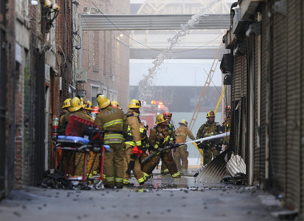 Los Angeles Fire Department firefighters work the scene of a structure fire that injured multiple firefighters, according to a fire department spokesman, Saturday, May 16, 2020, in Los Angeles. (AP Photo/Damian Dovarganes)