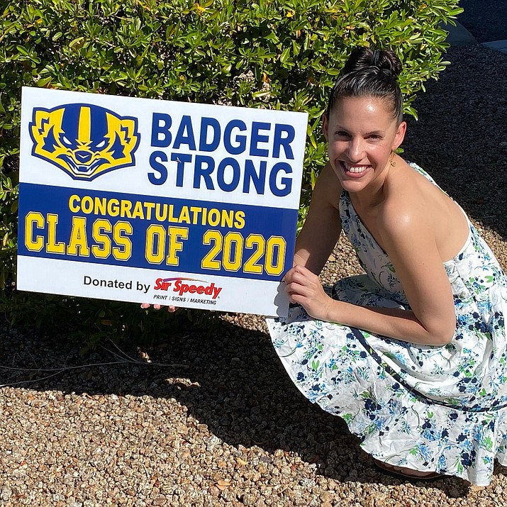 Prescott Sir Speedy shop owner Danielle Rickert kneels by one of the Badger Strong signs that she and her store employees at 1961 Commerce Center Circle recently designed and donated to the some 300 graduates of Prescott High School's Class of 2020. Rickert said it was important to honor the graduates whose senior year was impacted by the COVID-19 pandemic. (Danielle Rickert/Courtesy)
