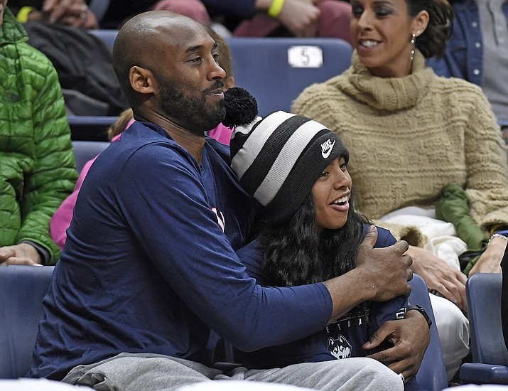 In this March 2, 2019, file photo, Kobe Bryant and his daughter Gianna watch the first half of an NCAA college basketball game between Connecticut and Houston in Storrs, Conn. Autopsy reports released Friday, May 15, 2020, show that the pilot who flew Bryant did not have drugs or alcohol in his system when the helicopter crashed in Southern California in January, killing all nine aboard. The causes of death for Bryant, his 13-year-old daughter Gianna, pilot Ara Zobayan and the others have been ruled blunt force trauma. Federal authorities are still investigating the Jan. 26 incident where the chopper crashed into the Calabasas hillsides. (Jessica Hill/AP, file)