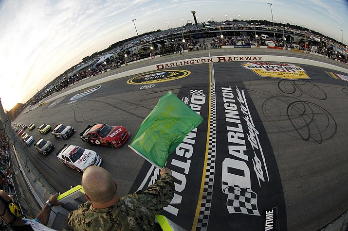 In this May 11, 2012, file photo, drivers take the green flag for the start of the NASCAR Nationwide Series auto race at Darlington Raceway in Darlington, S.C. NASCAR will re-fire the engines moments after mask-clad drivers climb into their cars at Darlington Raceway. The season will resume Sunday May 17, 2020, without spectators and drivers will have no practice before they pull away from pit road for the first time in more than two months. (Tyler Barrick/Pool Photo via AP, File)
