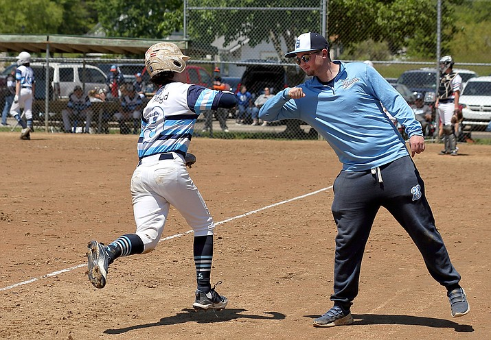 In this Saturday, May 9, 2020 photo, St. Louis Bears youth baseball players Mac Floyd, left, 14, gets a elbow bump from this brother and assistant coach Robby Floyd as Mac rounds the bases after smacking a homer during the Mother's Day Classic baseball tournament organized by GameTime Tournaments in Cottleville, Mo. (David Carson/St. Louis Post-Dispatch via AP)