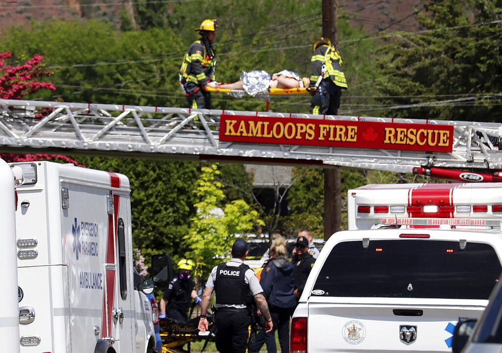 First responders carry an injured person on a stretcher across a fire truck ladder from a rooftop at the scene of a crash involving a Canadian Forces Snowbirds airplane in Kamloops, British Columbia, Sunday, May 17, 2020. (Brendan Kergin/Castanet Kamloops/The Canadian Press via AP)