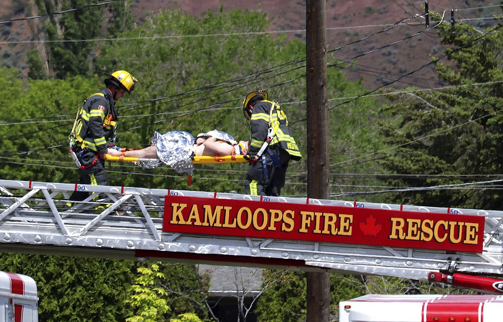 First responders carry an injured person on a stretcher across a fire truck ladder from a rooftop at the scene of a crash involving a Canadian Forces Snowbirds aircraft in Kamloops, British Columbia, Sunday, May 17, 2020. (Brendan Kergin/Castanet Kamloops/The Canadian Press via AP)