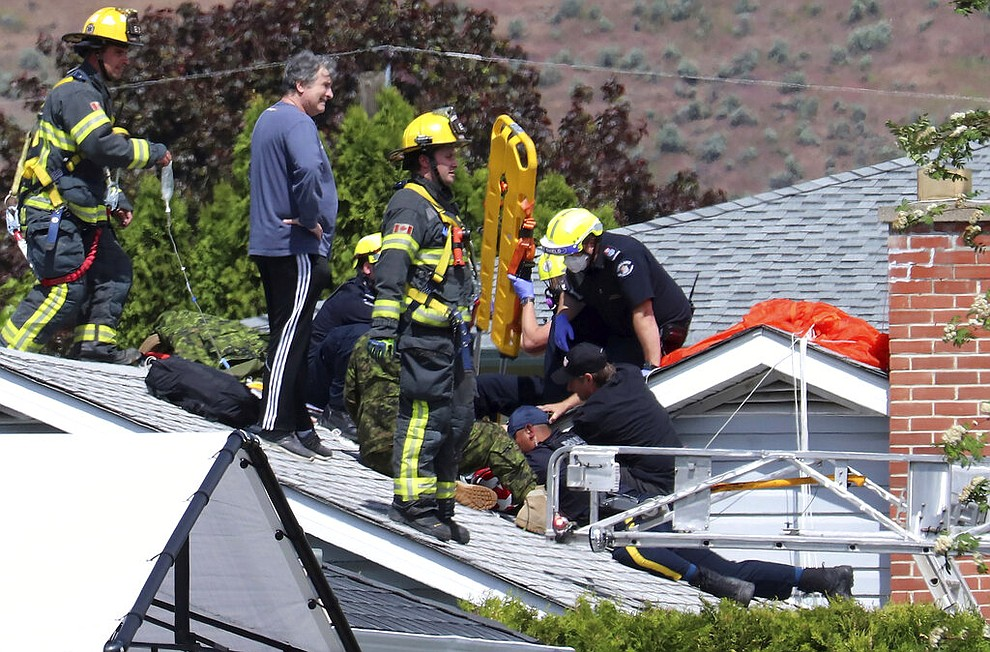 First responders attend to a person on a rooftop at the scene of a crash involving a Canadian Forces Snowbirds airplane in Kamloops, British Columbia, Sunday, May 17, 2020. (Brendan Kergin/Castanet Kamloops/The Canadian Press via AP)