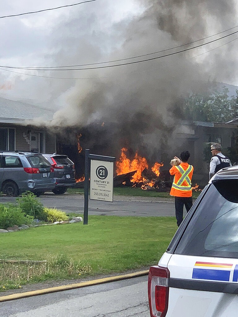 This photo provided by Elwood Delaney shows the scene of a crash involving a Canadian Forces Snowbirds airplane in Kamloops, Canada, Sunday, May 17, 2020. A Canadian acrobatic jet has crashed into the British Columbia neighborhood during a flyover intended to boost morale during the pandemic, killing at least one crew member and setting the house on fire. (Elwood Delaney via AP)