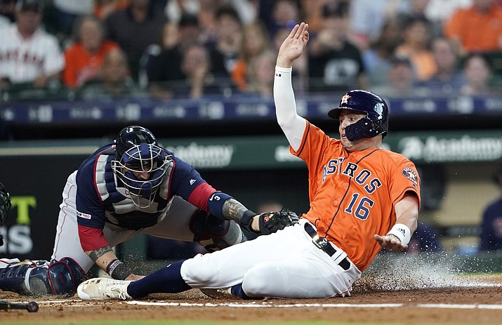 This May 24, 2019, file photo shows Houston Astros' Aledmys Diaz (16) scoring as Boston Red Sox catcher Sandy Leon reaches to tag him at home plate during the second inning of a baseball game in Houston. The Astros were scheduled to play the Red Sox in the first of consecutive weekend series matching teams that fired World Series-winning managers in the aftermath of a sign-stealing scandal. (David J. Phillip/AP, file)