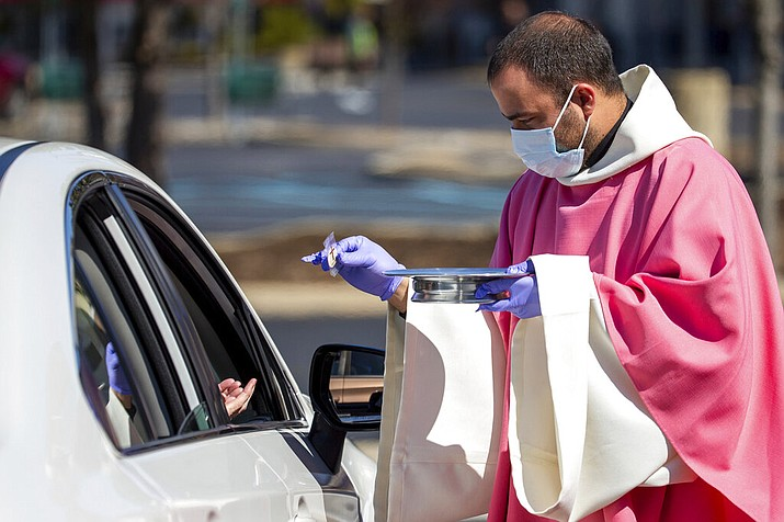 In this Sunday, March 22, 2020 file photo, the Rev. William A. Mentz, pastor of the Scranton, Pa.-based St. Francis and Clare Progressive Catholic Church, wears a mask and gloves while distributing prepackaged communion to the faithful attending Mass while sitting in their cars in the parking lot of a shopping center in Moosic, Pa. The Progressive Catholic Church is a small denomination operating independently of the Roman Catholic Church. Other Catholic churches in the Scranton area suspended the celebration of mass to help control the spread of COVID-19. (Christopher Dolan/The Times-Tribune via AP)