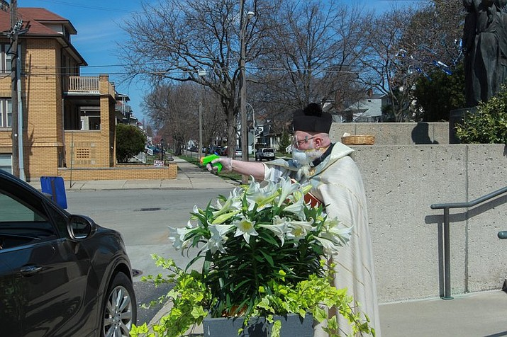 In this Saturday, April 11, 2020 file photo, Rev. Timothy Pelc blesses Easter baskets outside St. Ambrose Church in Grosse Pointe Park, Mich. Pelc, wearing church vestments and protective gear, offered a prayer and sprayed holy water from a squirt gun instead of blessing baskets inside the church in a bid to maintain social distancing during the coronavirus pandemic. (Natalie White via AP)