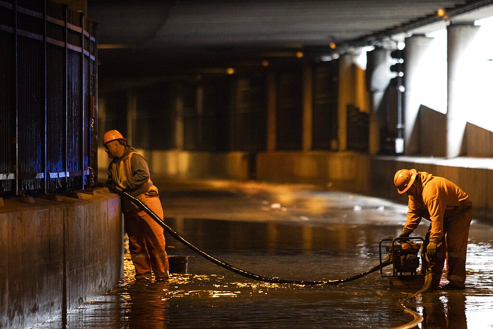 City workers remove water from Lower Wacker Drive near Randolph Street after overnight flooding, Monday, May 18, 2020 in Chicago. (Ashlee Rezin Garcia/Chicago Sun-Times via AP)