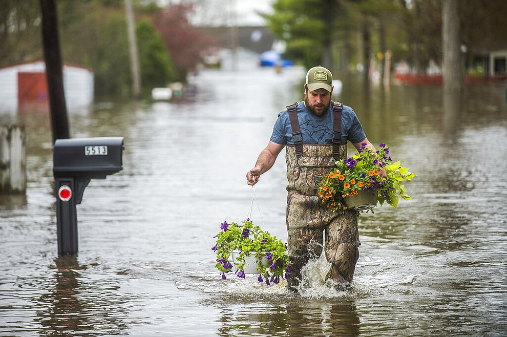 Tyler Marciniak of Grand Rapids carries hanging plants through floodwater as he helps his father, Tom Marciniak, assess the damage to his home on Red Oak Drive on Wixom Lake, Tuesday, May 19, 2020 in Beaverton, Mich. (Katy Kildee/Midland Daily News via AP)