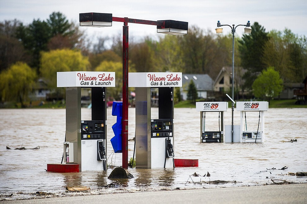 Floodwater surrounds gas pumps at Wixom Lake Gas & Launch Tuesday, May 19, 2020 along the Tittabawassee River in Beaverton, Mich. (Katy Kildee/Midland Daily News via AP)