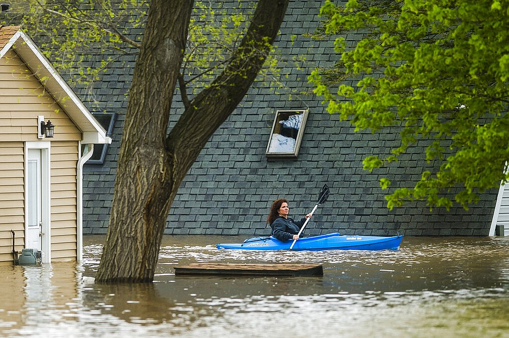 People use kayaks to assess the damage at homes in their neighborhood on Oakridge Road on Wixom Lake, Tuesday, May 19, 2020 in Beaverton, Mich. (Katy Kildee/Midland Daily News via AP)