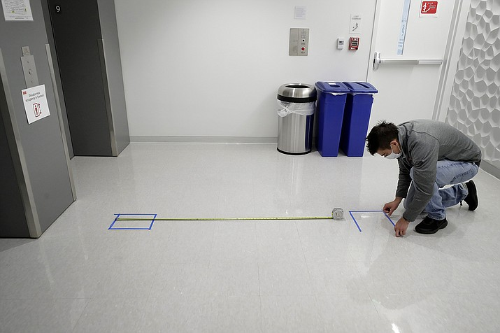 Kevin Gonzales, director of operations at the Rajen Kilachand Center for Integrated Life Sciences and Engineering, at Boston University, places safe distancing floor markings near an elevator on the school's campus, in Boston, Thursday, May 21, 2020. Boston University is among a growing number of universities making plans to bring students back to campus this fall, but with new measures meant to keep the coronavirus at bay. (AP Photo/Steven Senne)
