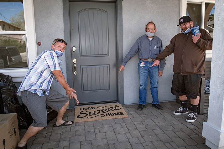 "Left to right, Ryan Belk, John Stevens and Danny Cedergreen point to a ""Home Sweet Home"" mat at the front door of Stevens' new home. (Blushing Cactus Photography/Courtesy)"
