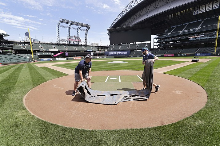 Grounds crew workers Jacob Weiderstrom, left, and Marcus Gignac pull a tarp off home plate as they continue to keep the Seattle Mariners' field in playing shape as the ballpark goes into its seventh week without baseball played because of the coronavirus outbreak Monday, May 11, 2020, in Seattle. A person familiar with the decision tells The Associated Press that Major League Baseball owners have given the go-ahead to making a proposal to the players' union that could lead to the coronavirus-delayed season starting around the Fourth of July weekend in ballparks without fans. (Elaine Thompson/AP)