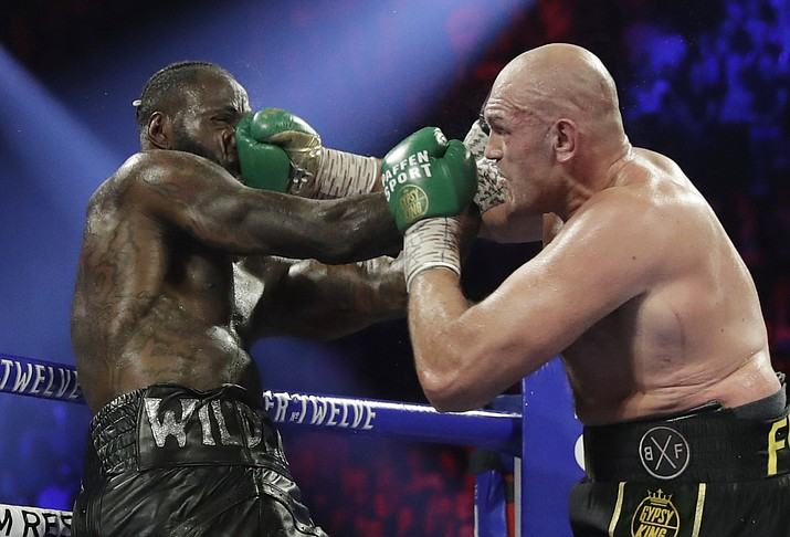 In this Feb. 22, 2020, file photo, Tyson Fury, of England, lands a right to Deontay Wilder, left, during a WBC heavyweight championship boxing match in Las Vegas. Boxing promoter Bob Arum says he plans to stage a card of five fights on June 9 at the MGM Grand. It's the first of a series of fights over the next two months at the Las Vegas hotel. A second fight card will be held two nights later. ESPN will televise both cards to kick off twice weekly shows at the hotel in June and July. The fights are pending approval of the Nevada Athletic Commission. (Isaac Brekken/AP, file)