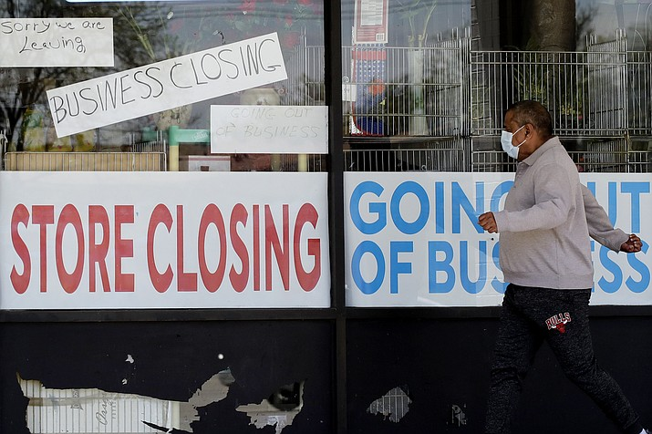 A man looks at signs of a closed store due to COVID-19 in Niles, Ill., Thursday, May 21, 2020. More than 2.4 million people applied for U.S. unemployment benefits last week in the latest wave of layoffs from the viral outbreak that triggered widespread business shutdowns two months ago and sent to economy into a deep recession. (Nam Y. Huh/AP)