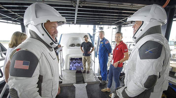 In this Aug. 13, 2019 file photo, NASA astronauts Doug Hurley, left, and Bob Behnken work with teams from NASA and SpaceX to rehearse crew extraction from SpaceX's Crew Dragon, which will be used to carry humans to the International Space Station, at the Trident Basin in Cape Canaveral, Fla. For the first time in nearly a decade, astronauts are about to blast into orbit aboard an American rocket from American soil. And for the first time in the history of human spaceflight, a private company -- SpaceX -- is providing the ride. (Bill Ingalls/NASA)