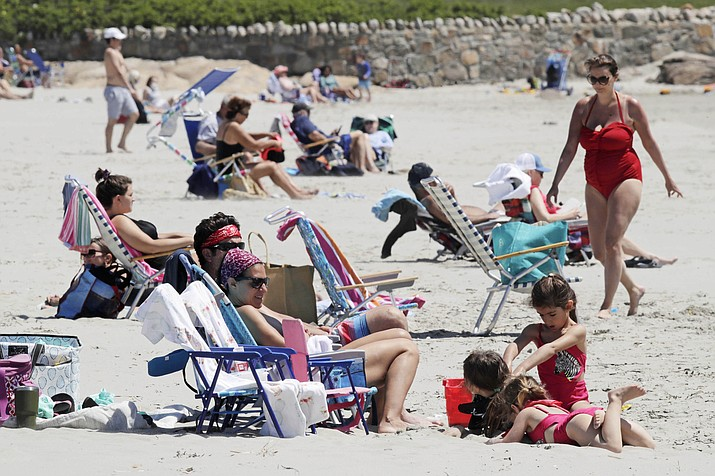 Beachgoers relax on the shore at Good Harbor Beach in Gloucester, Mass., Friday, May 22, 2020. Beaches in Gloucester reopened with restrictions on Friday after being closed two months ago due to the pandemic. (Charles Krupa/AP)