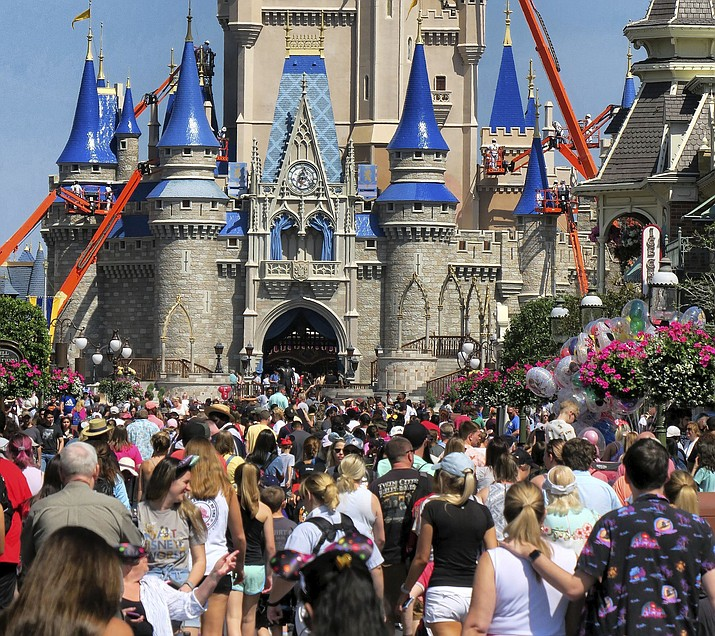 In this March 12, 2020 photo, a crowd is shown along Main Street USA in front of Cinderella Castle in the Magic Kingdom at Walt Disney World in Lake Buena Vista, Fla. The NBA is reportedly in talks with Disney to resume play at the ESPN Wide World of Sports Complex, which Disney owns in Orlando. (Joe Burbank/Orlando Sentinel via AP, File)