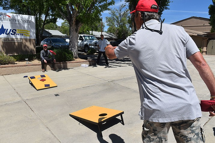 U.S. veteran Joe Trompeter tosses a bean bag in a cornhole game in front of the Liberty Pointe veterans center in Prescott on Friday, May 22, 2020. (Jesse Bertel/Courier)