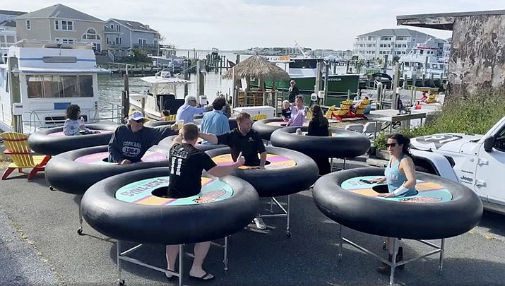 """In this image made from Saturday, May 16, 2020, video provided by Revolution Event Design & Production, """"bumper tables,"""" created by the company and designed to allow people to practice social distancing while eating and talking, are debuted at Fish Tales, a restaurant in Ocean City, Md. (Katie Kirby/Revolution Event Design & Production via AP)"""