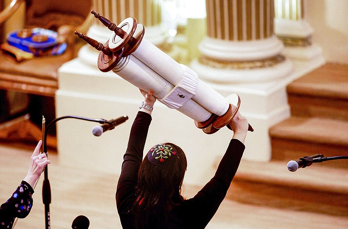 In this Feb. 1, 2020, file photo, Rabbi Jacqueline Mates-Muchin holds a Torah scroll aloft during Shabbat morning service at Temple Sinai in Oakland, Calif. The California Department of Public Health released Monday, May 25, a framework under which county health departments can approve the reopening of churches, mosques, synagogues and other houses of worship that have mostly shuttered their doors since Gov. Gavin Newsom's March stay-at-home order designed to slow the spread of the coronavirus. (AP Photo/Noah Berger, File)