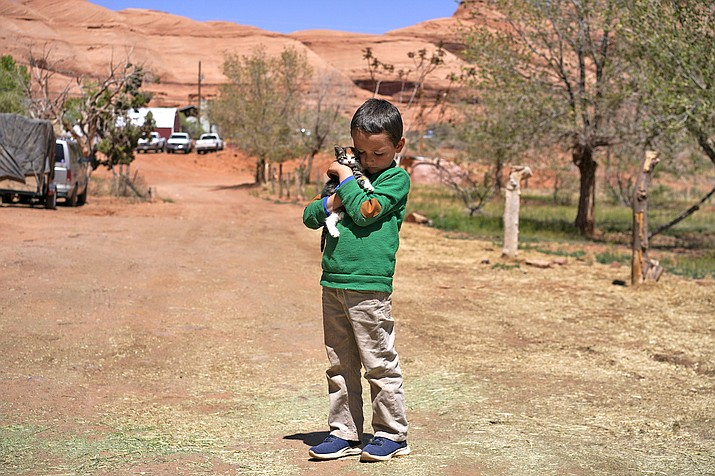 """A boy holds a kitten named """"Popcorn Ball"""" in front of his home in Oljato-Monument Valley, Utah, on the Navajo reservation April 27. The reservation has some of the highest rates of coronavirus in the country. If Navajos are susceptible to the virus' spread in part because they are so closely knit, that's also how many believe they will beat it. (AP Photo/Carolyn Kaster)"""
