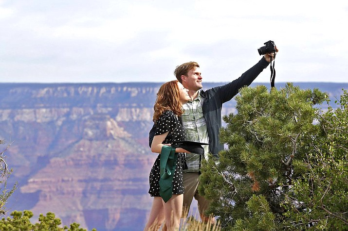 Recent Baylor University graduate Cady Malachowski takes a photo with Andrew Fink at the Grand Canyon May 15. Tourists are once again roaming portions of Grand Canyon National Park when it partially reopened May 15, despite objections that the action could exacerbate the coronavirus pandemic. (AP Photo/Matt York)