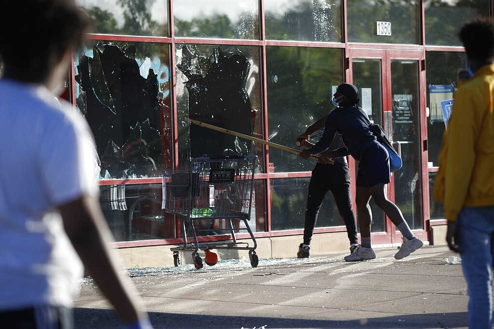 A man breaks a window at a tire store Thursday, May 28, 2020, in St. Paul, Minn. Minnesota Gov. Tim Walz called in the National Guard on Thursday as looting broke out in St. Paul and a wounded Minneapolis braced for more violence after rioting over the death of George Floyd, a handcuffed black man in police custody, reduced parts of one neighborhood to a smoking shambles. (AP Photo/John Minchillo)