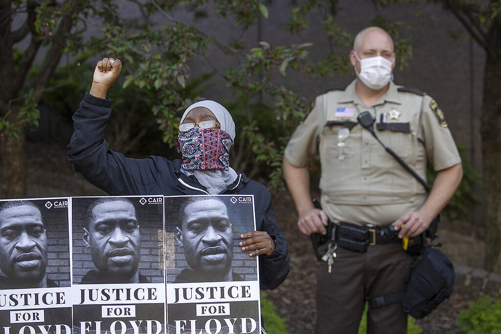 A protester holds a sign during a demonstration at the Government Center in support of the Minnesota chapter of the Council on American-Islamic Relations' call for the arrest of the police involved in Monday's death of George Floyd, Thursday, May 28, 2020, in Minneapolis. (Elizabeth Flores/Star Tribune via AP)