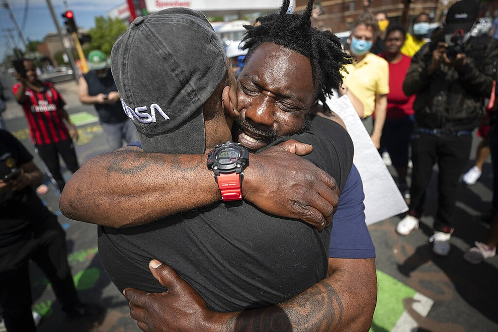 Former Minnesota Gopher and NFL football player Tyron Carter pleads with protesters not to tear up their city, as he hugs Tony L. Clark, foreground, at the site where George Floyd died Monday in the custody of Minneapolis police, Thursday, May 28, 2020, in Minneapolis. (Jerry Holt/Star Tribune via AP)