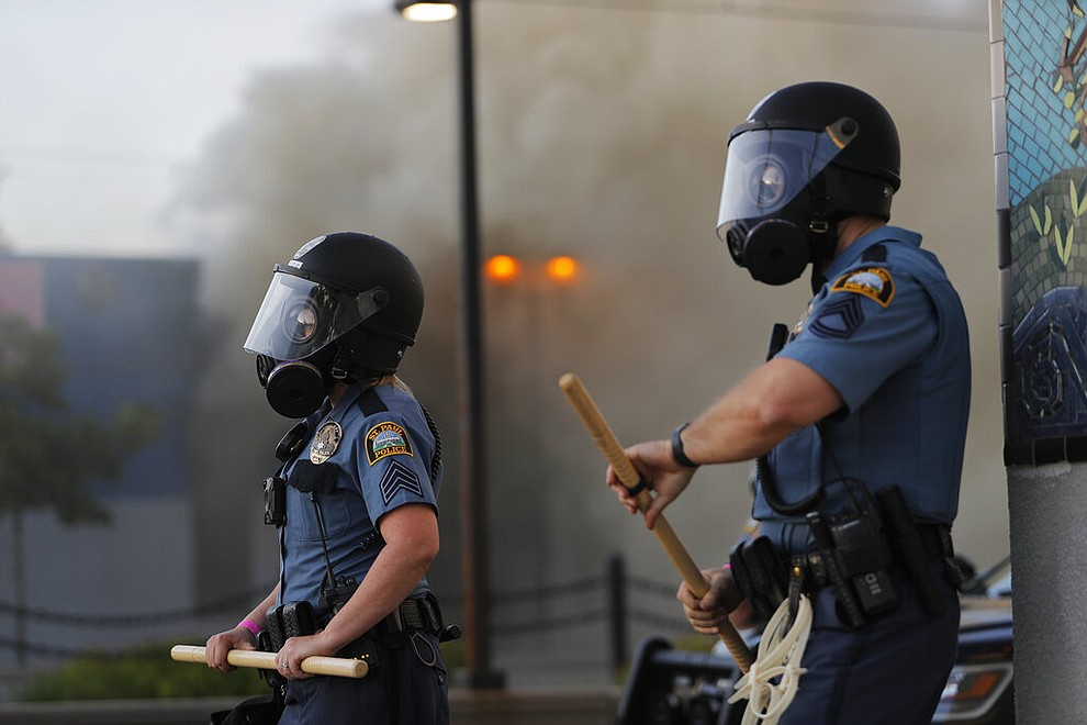 St. Paul police watch demonstrators Thursday, May 28, 2020, in St. Paul, Minn. Protests over the death of George Floyd, a handcuffed black man who died in police custody, broke out in Minneapolis for a third straight night. (AP Photo/Julio Cortez)