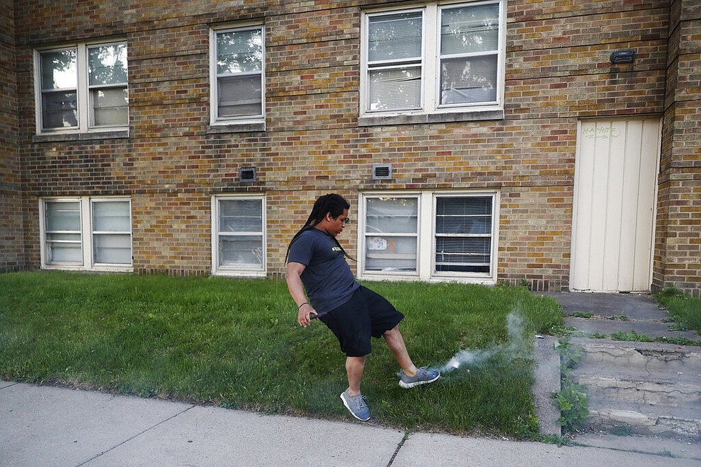 A man kicks at a can of tear gas Thursday, May 28, 2020, in St. Paul, Minn. Protests over the death of George Floyd, a handcuffed black man who died in police custody, broke out in Minneapolis for a third straight night. (AP Photo/John Minchillo)