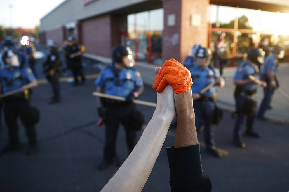 Demonstrators join hands Thursday, May 28, 2020, in St. Paul, Minn. Protests over the death of George Floyd, a black man who died in police custody, broke out in Minneapolis for a third straight night. (AP Photo/John Minchillo)