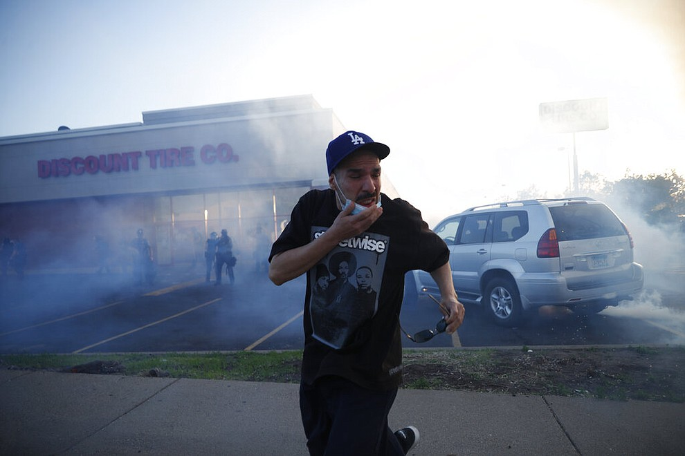 A demonstrator runs from tear gas Thursday, May 28, 2020, in St. Paul, Minn. Protests over the death of George Floyd, a black man who died in police custody, broke out in Minneapolis for a third straight night. (AP Photo/John Minchillo)