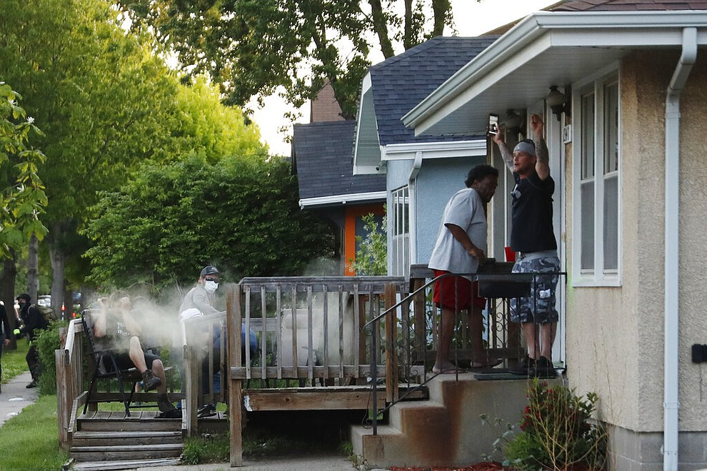 People react as a round of tear gas lands on a porch Thursday, May 28, 2020, in St. Paul, Minn. Protests over the death of George Floyd, a black man who died in police custody, broke out in Minneapolis for a third straight night. (AP Photo/John Minchillo)