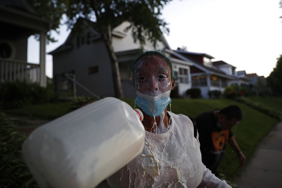 A demonstrator washes her eyes Thursday, May 28, 2020, in St. Paul, Minn. Protests over the death of George Floyd, a black man who died in police custody, broke out in Minneapolis for a third straight night. (AP Photo/John Minchillo)