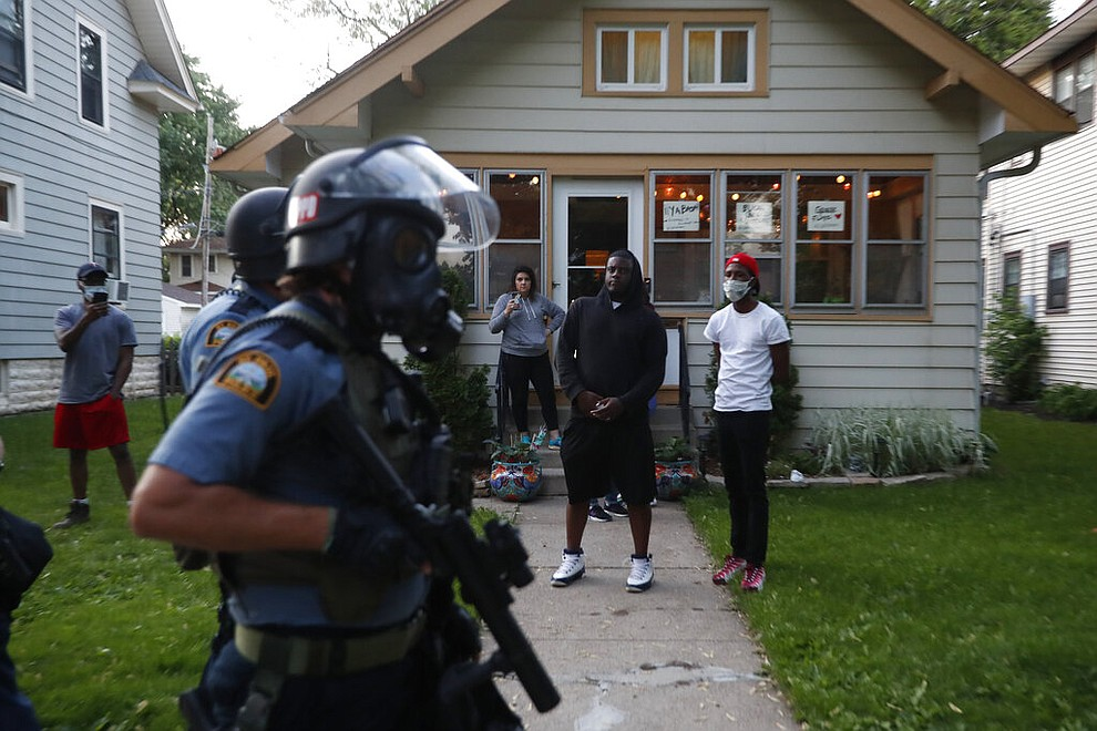 Bystanders watch as police walk down a street Thursday, May 28, 2020, in St. Paul, Minn. Protests over the death of George Floyd, a black man who died in police custody, broke out in Minneapolis for a third straight night. (AP Photo/John Minchillo)
