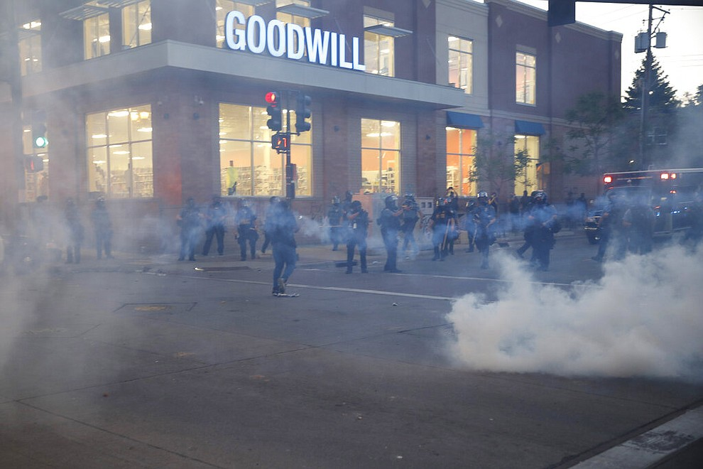 Authorities release tear gas Thursday, May 28, 2020, in St. Paul, Minn. Protests over the death of George Floyd, a black man who died in police custody, broke out in Minneapolis for a third straight night. (AP Photo/John Minchillo)