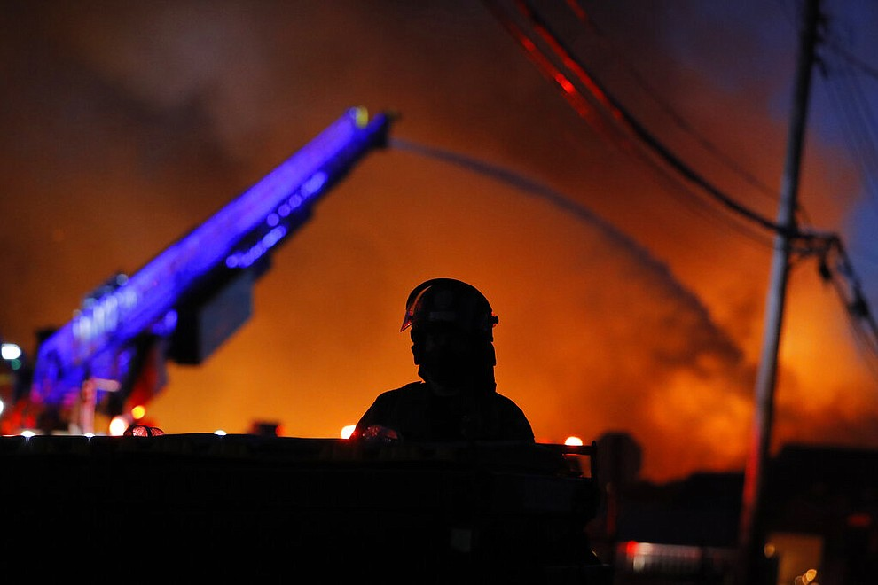 A police remain on watch as firefighters work during demonstrations Thursday, May 28, 2020, in St. Paul, Minn. Protests over the death of George Floyd, the black man who died in police custody broke out in Minneapolis for a third straight night. (AP Photo/Julio Cortez)