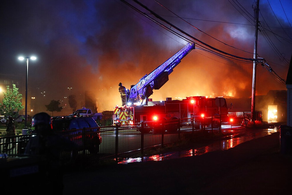 Firefighters work the scene of a structure fire that occurred during demonstrations Thursday, May 28, 2020, in St. Paul, Minn. Protests over the death of George Floyd, the black man who died in police custody broke out in Minneapolis for a third straight night. (AP Photo/John Minchillo)