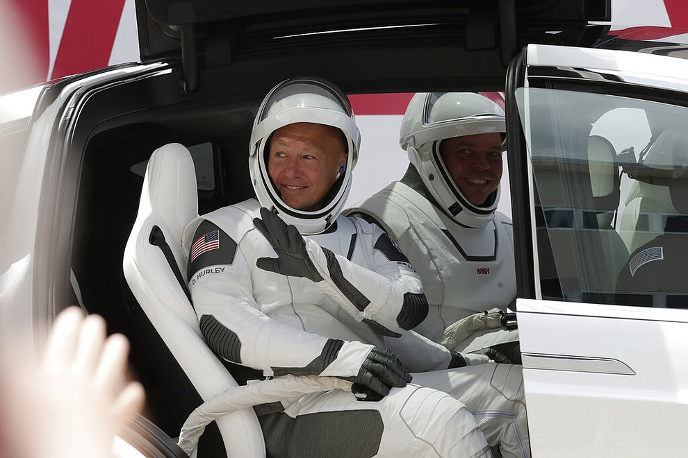 NASA astronauts Douglas Hurley, left, and Robert Behnken wave while seated in a Tesla SUV on their way to Pad 39-A, at the Kennedy Space Center in Cape Canaveral, Fla., Saturday, May 30, 2020. The two astronauts will fly on a SpaceX test flight to the International Space Station. For the first time in nearly a decade, astronauts will blast into orbit aboard an American rocket from American soil, a first for a private company. (AP Photo/John Raoux)