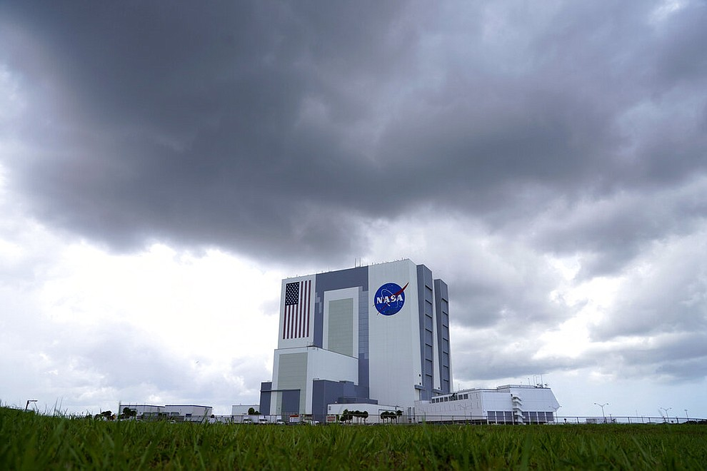 Storm clouds pass over the Vehicle Assembly Building as a SpaceX Falcon 9, with NASA astronauts Doug Hurley and Bob Behnken in the Crew Dragon capsule, sits on Launch Pad 39-A at the Kennedy Space Center in Cape Canaveral, Fla., Saturday, May 30, 2020. The two astronauts are on the SpaceX test flight to the International Space Station scheduled to liftoff Saturday. (AP Photo/David J. Phillip)