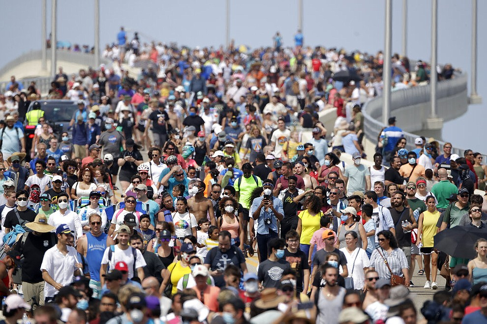 Spectators walk from their vantage point on a bridge in Titusville, Fla. after watching SpaceX Falcon 9 lift off with NASA astronauts Doug Hurley and Bob Behnken in the Dragon crew capsule, Saturday, May 30, 2020 from the Kennedy Space Center at Cape Canaveral, Fla. The two astronauts are on the SpaceX test flight to the International Space Station. For the first time in nearly a decade, astronauts blasted towards orbit aboard an American rocket from American soil, a first for a private company. (AP Photo/Charlie Riedel)