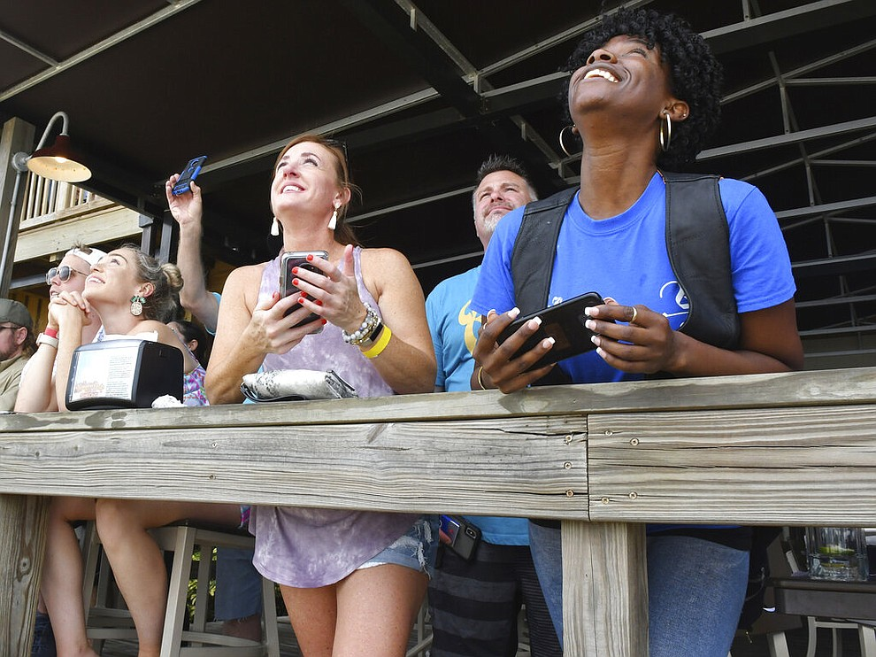 Spectators at Shiloh's Steak & Seafood restaurant in Titusville, Fla. watching the launch of the SpaceX rocket, Saturday, May 30, 2020. (Tim Shortt/Florida Today via AP)