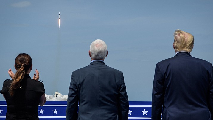 U.S. Vice President Mike Pence, left,  and President Donald Trump watch a rocket ship blast off. (Official NASA photo/Public domain)