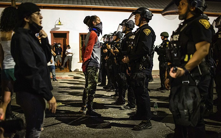 In this Friday, May 29, 2020, photo, protesters stand off against a line of officers from the Tucson Police Department at Cushing Street and Church Avenue in Tucson, Ariz. The protest in Tucson was similar to those in numerous cities across the United States following George Floyd's death while in custody of the Minneapolis police in Minnesota earlier this week. (Josh Galemore/Arizona Daily Star via AP)